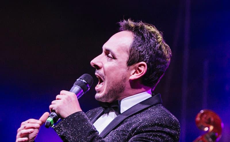 Il crooner Matteo Brancaleoni con un microfono mentre canta dal vivo